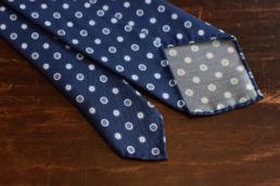 Cravate bleue à pois bleus. Construction 3 plis non doublée et roulotée à la main sur les bords. Motif imprimé à pois et ronds bleus